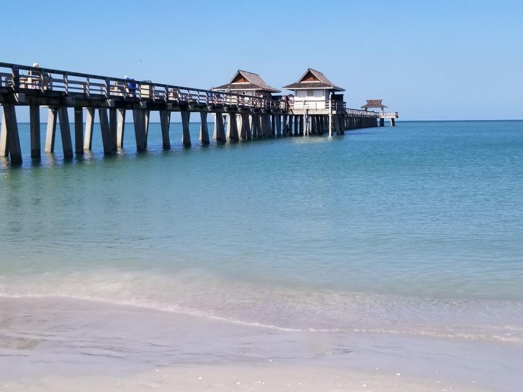 Historic Naples Pier is a free Naples attraction you can't miss while in Naples Florida. You'll love the stroll out into the ocean to watch sunset, seagulls and even dolphins swim by. It's also a great spot to fish or have an ice cream with the kids. #naplespier #naplesflorida