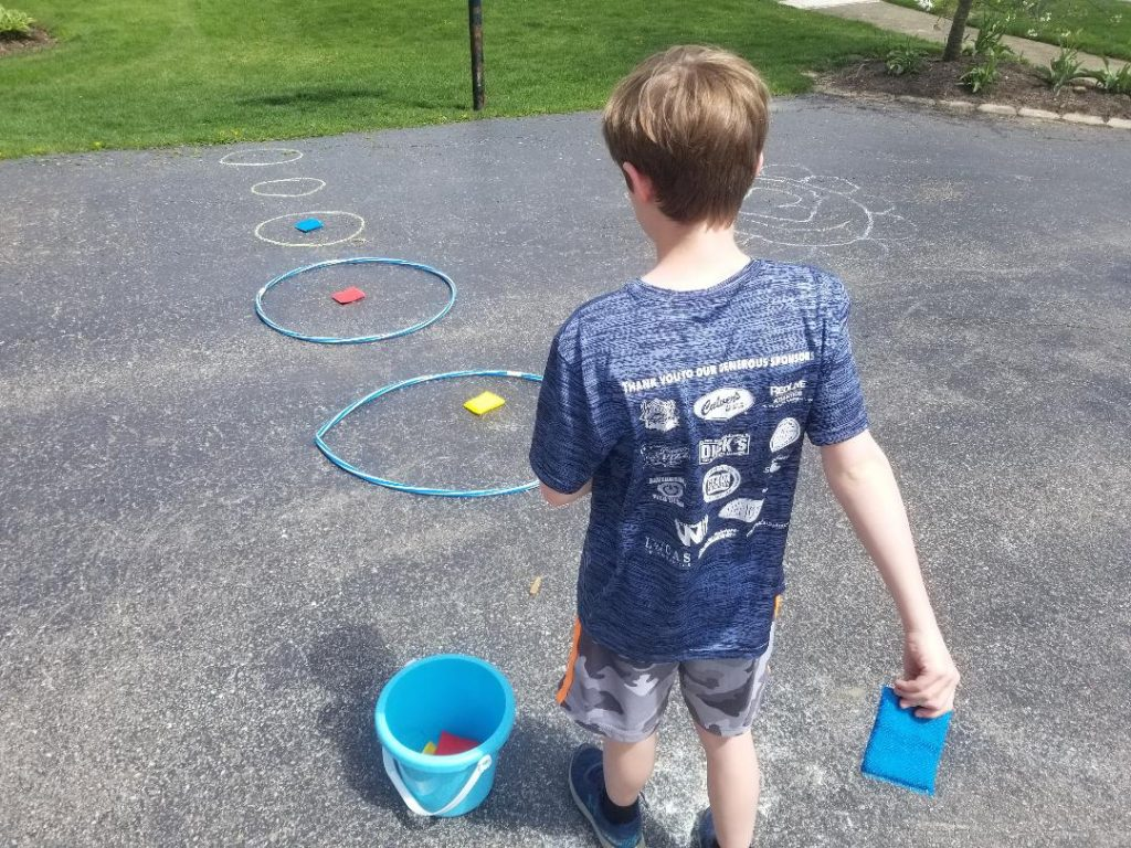 Outdoor Game for Kids - Sponge Toss. All you need is wet sponges, hula hoops and a bucket. Or just draw the circles with chalk.