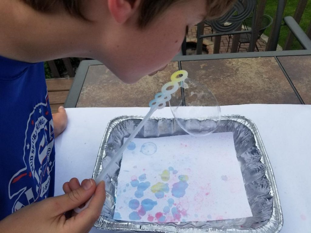 Blowing bubbles to create bubble art for kids