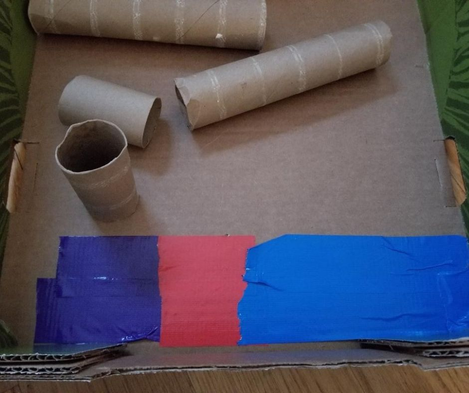 Make the base of your DIY Cardboard Marble run with colorful tape.