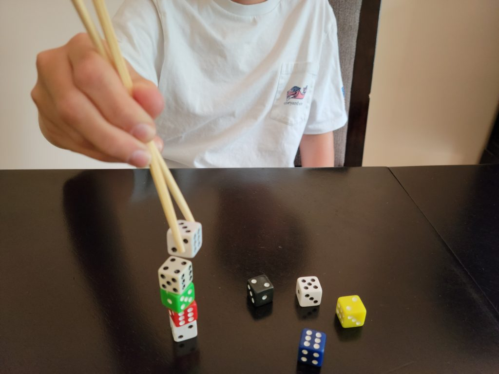 Teens can Stack the Dice in this fun Minute to Win it Game. All you need for this challenge is dice and chopsticks.