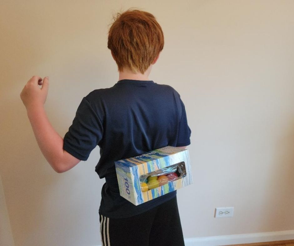 Hilarious Junk in the Trunk Challenge for kids parties with Kleenex box, belt and ping pong balls. A great Minute to Win It game.