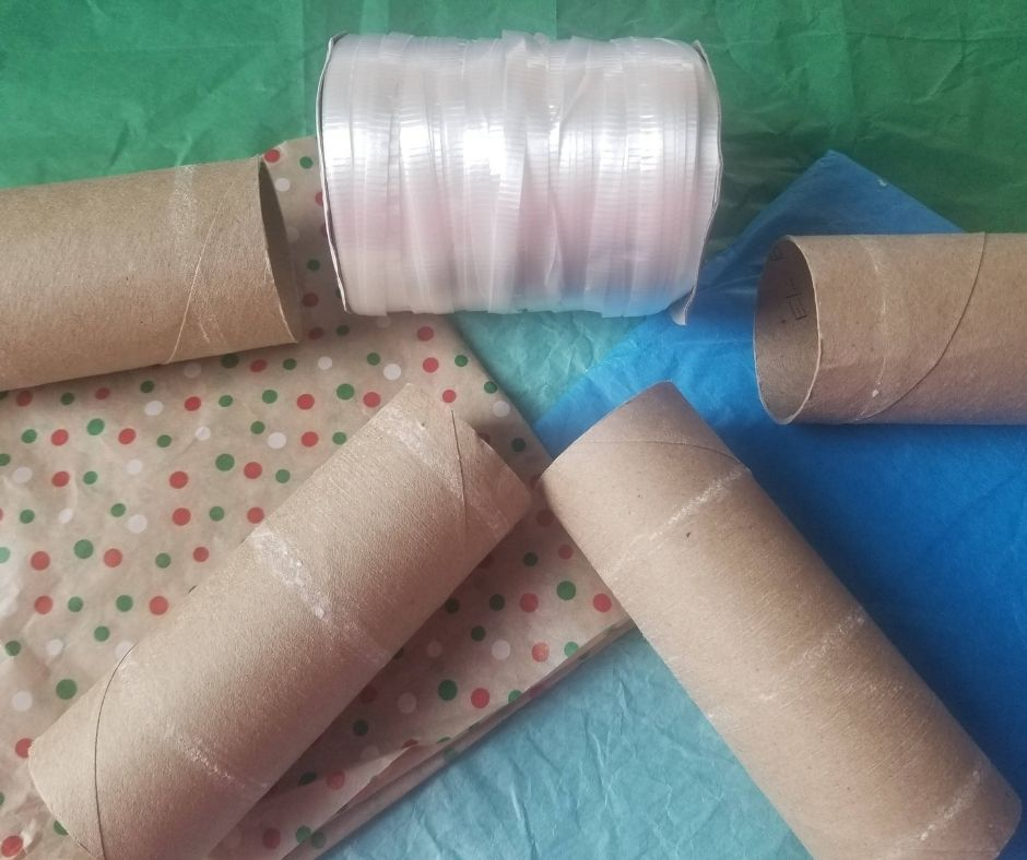 Supplies to make your Confetti Party Poppers at home. All you need is toilet paper rolls, tissue paper, and ribbon..