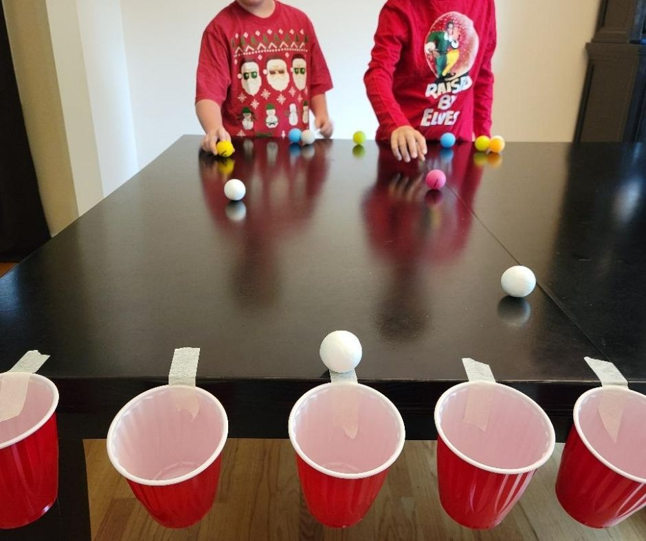 Easy Minute to Win It Game for Families Drop in the Cup. Make it a Christmas party game with ping pong balls as snowballs and red solo cups. A fun addition to any holiday party.