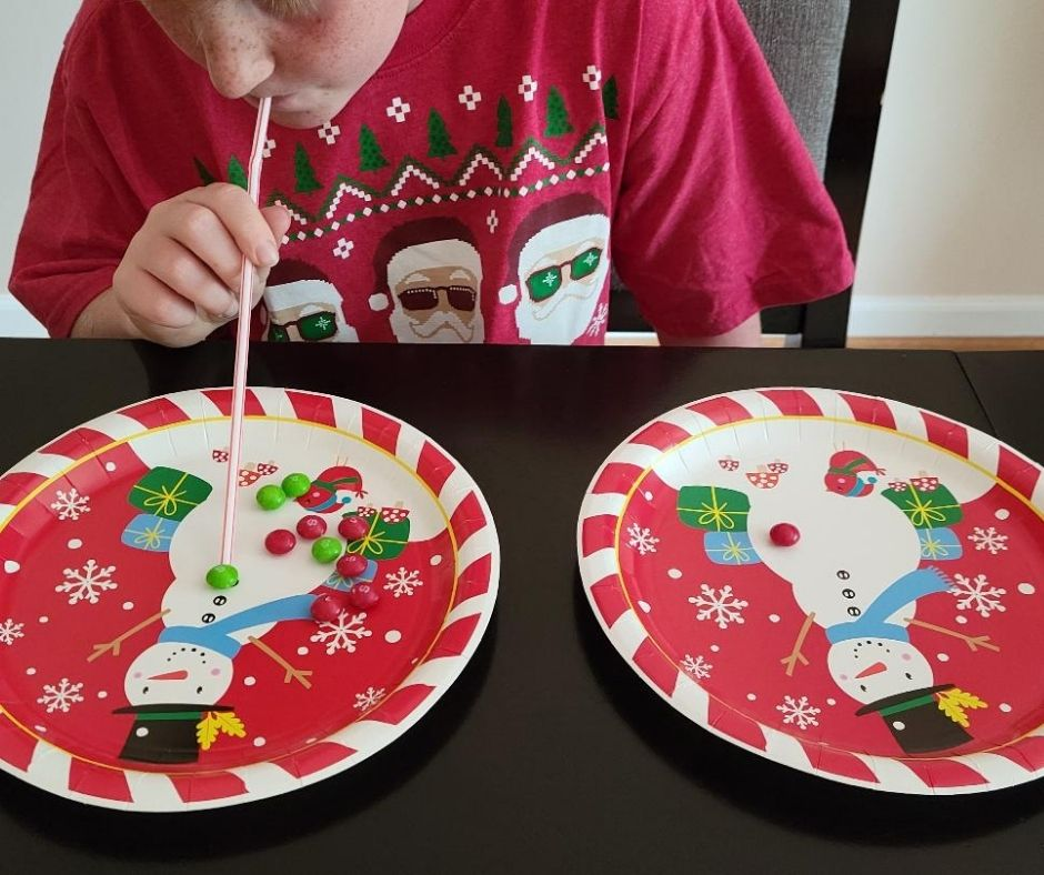 Fun Christmas Minute to Win it Game Suck it Up. Quick party game with M&Ms or Skittles, a straw and paper plates. Kids will love the challenge of this fun Holiday game.