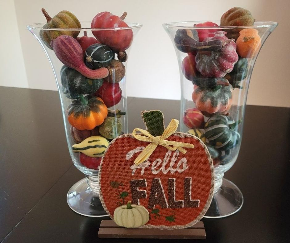 Easy DIY Fall Decor Ideas with Pumpkins and a Vase. Pick up plastic pumpkins and gourds at Dollar Tree and add them to a clear vase. Then place a cute Fall, Halloween or Thanksgiving sign in front of the vase and your Fall table decorations are set. It's a cheap an simple fall décor idea any one can create.